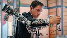 Посетитель тестирует экзоскелет на Innorobo 2014 в Лионе