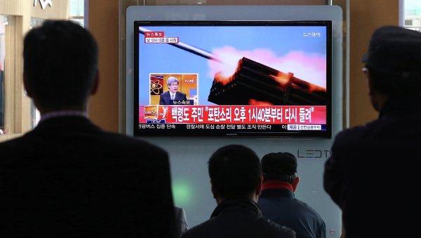 Люди смотрят выпуск новостей в Сеуле. 31 марта 2014