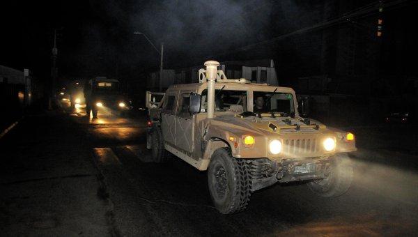 Военный конвой патрулирует дорогу в городе Икике после цунами