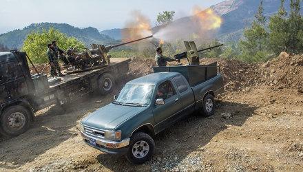 Военнослужащие сирийской армии ведут огонь возле захваченного исламистами города Кесаб