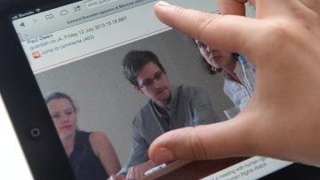 Журналист смотрит на экран компьютера, на котором открыта фотография экс-сотрудника ЦРУ Эдварда Сноудена. Архивное фото