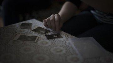 Крымская татарка показывает фотографии членов своей семьи, депортированной из Крыма. Архивное фото
