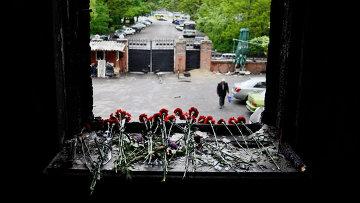 Цветы на разбитом окне в память о погибших в результате пожара в Доме профсоюзов на площади Куликово поле в Одессе, архивное фото