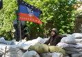 Активист сил самообороны сторонников федерализации Украины на баррикаде под флагом ДНР