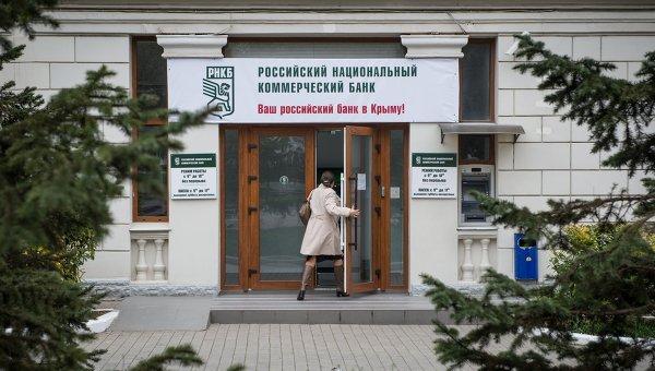 Женщина входит в здание Российского национального коммерческого банка в городе Севастополе, архивное фото