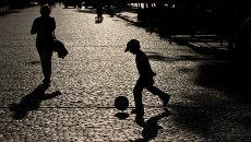 Ребенок играет в мяч на улице. Архивное фото