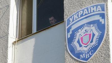 Милиционер смотрит из окна здания областного управления МВД Украины