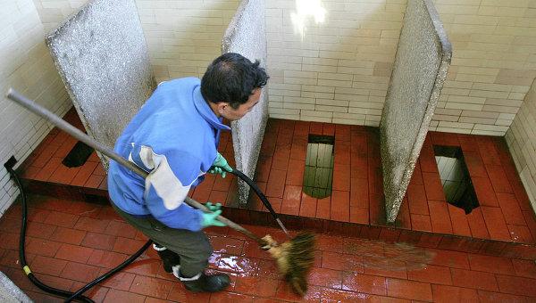 Работник очищает общественный туалет в Китае,архивное фото