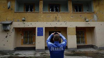 Местный житель фотографирует фасад здания министерства юстиции в Краматорске, которое подверглось артиллерийскому обстрелу украинской армией, архивное фото