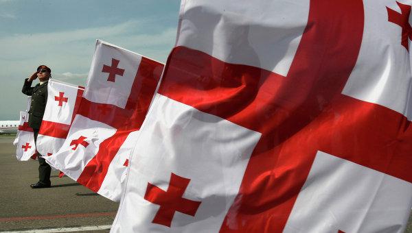 Грузинский военный на фоне флагов. Архивное фото