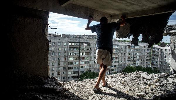 Мужчина в жилом доме, пострадавшем от артиллерийского обстрела в Луганске