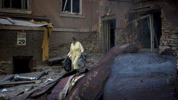 Женщина во дворе разрушенного артиллерийским обстрелом дома в Луганске. Архивное фото