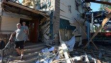 Местные жители выходят из дома, пострадавшего во время ракетно-минометного обстрела Горловки