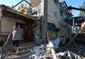 Местные жители выходят из дома, пострадавшего во время ракетно-минометного обстрела Горловки в Донецкой области