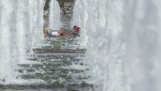 Жители Москвы спасаются от жары у фонтана на Поклонной горе