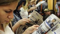 Люди читают газеты в метро в Киеве, Украина. Архивное фото