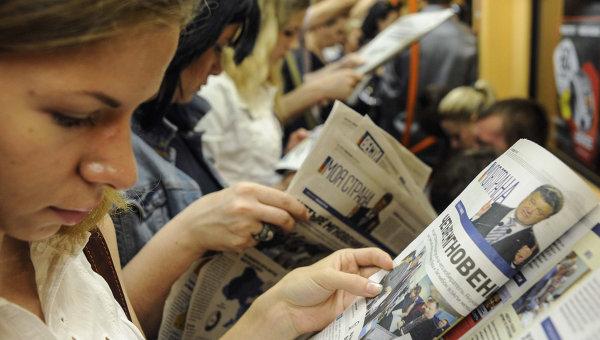 Люди читают газеты в метро в Киеве, Украина