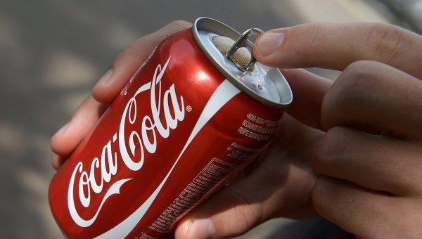 Покупатель держит банку с напитком компании Coca-Cola. Архивное фото