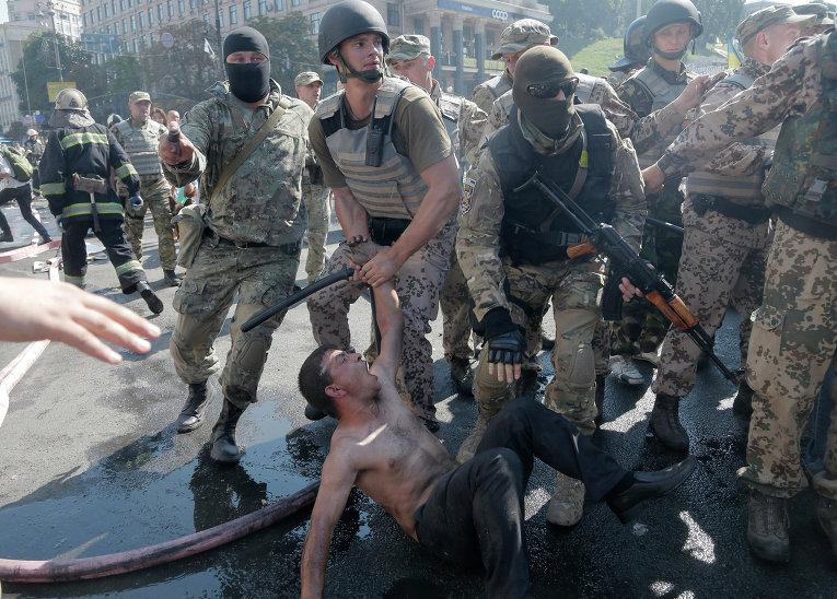 Сотрудники спецподразделений задерживают активиста во время беспорядков в Киеве на Площади Независимости