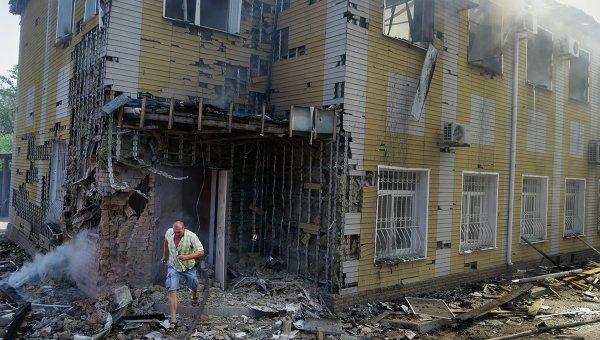 Мужчина выбегает из разрушенного в результате обстрела украинскими силовиками дома в Донецке