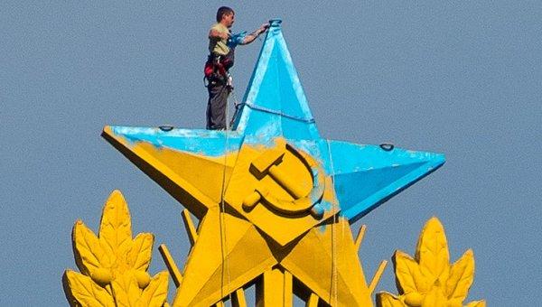 Рабочий закрашивает звезду на шпиле высотного здания на Котельнической набережной в Москве