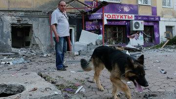 Мужчина с собакой рядом с поврежденным в результате обстрела зданием в Донецке