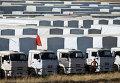 Водитель стоит возле грузовиков гуманитарного конвоя в Украину из России в Ростовской области