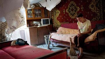 Жительница Донецка в своей разрушенной обстрелом квартире. Архивное фото.