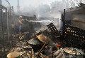 Житель Донецка тушит пожар в своем доме после обстрела
