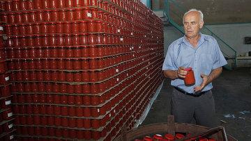 Фермер из Молдовы в хранилище с банками томатной пасты. Гырбовец, Молдова