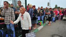 Украинские беженцы стоят в очереди на границе для возвращения в свои дома. 17 сентября 2014 года