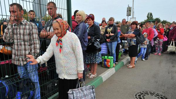 Украинские беженцы стоят в очереди на границе для возвращения в свои дома