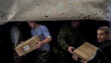 Мужчины разгружают один из грузовиков гуманитарной колонны на Украине. Архивное фото