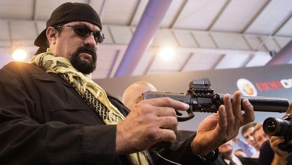 Знаменитый американский актер Стивен Сигал с самозарядным пистолетом Сердюкова с глушителем во время посещения международной выставки Оборонэкспо-2014