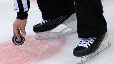 Судья держит шайбу перед вбрасыванием в матче регулярного чемпионата КХЛ. Архивное фото
