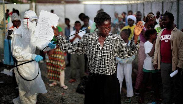 Женщину с выпиской из лечебного центра опрыскивают с целью дезинфекции от лихорадки Эбола, Монровия. 30 сентября 2014