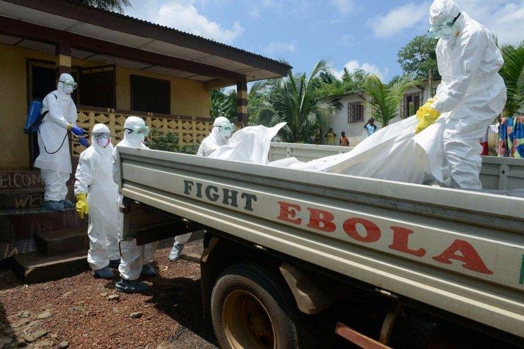 Либерийский персонал Красного Креста переносит тело погибшего от лихорадки Эбола в грузовик. Монровия, 4 сентября 2014