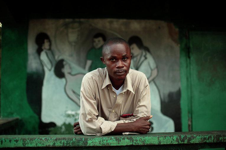 Джулиус Прут, выживший после заражения лихорадкой Эбола на пороге медицинского центра в Монровии. Либерия, 28 сентября 2014