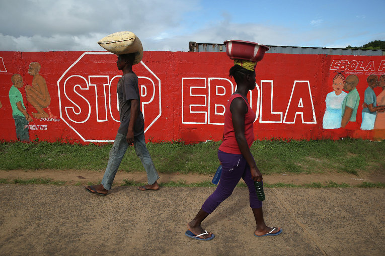 Жители Монровии проходят мимо стены с описанием симптомов лихорадки Эбола. Либерия, 2 октября 2014