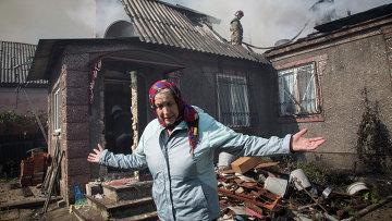 Жительница Донецка рядом со своим домом после артобстрела