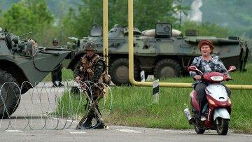 Женщина на скутере проезжает КПП украинской армии по дороге в деревню Спиваковка Луганской области. Архивное фото