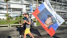Зрители несут флаг с портретом гонщика команды Торо Россо Даниила Квята