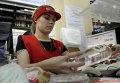 Кассир пробивает водку в одном из магазинов Омска
