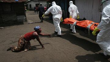 Члены команды захоронения несут тело женщины, умершей от Эболы в Либерии. Архивное фото