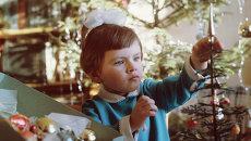 Скоро Новый год. Девочка украшает елку