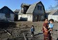 Женщина с детьми у своего дома, пострадавшего в результате артиллерийского обстрела украинскими силовиками города Донецка