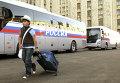 Мальчик идет возле автобуса перед отправлением на отдых