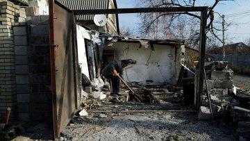 Мужчина в гараже, поврежденном в результате обстрела поселка Красный пахарь