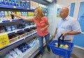 Покупатели у полки с молочной продукцией в магазине