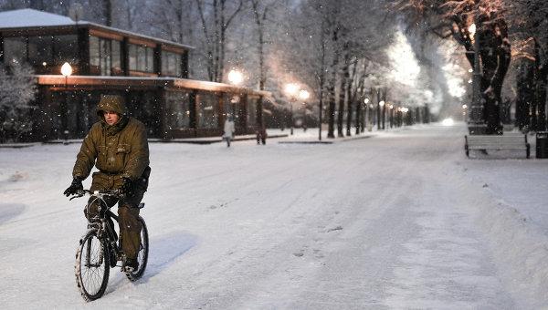 Человек едет на велосипеде во время снегопада в Москве. Архивное фото
